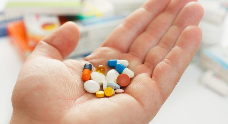 Stos tabletek i kapsułek leżących na dłoni.