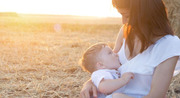 Kobieta karmi dziecko piersią.