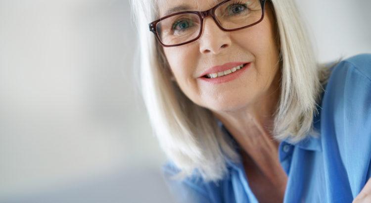Uśmiechnięta starsza pani w okularach.
